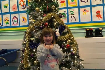 Child in front of our Christmas tree at our Christmas Fayre.