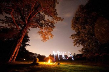 Outdoors at night, using torch to draw 'YMCA'.